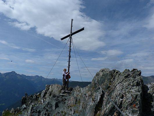 Nils am Gipfelkreuz vom Auernig. Im Hintergrund die Kreuzeckgruppe.
