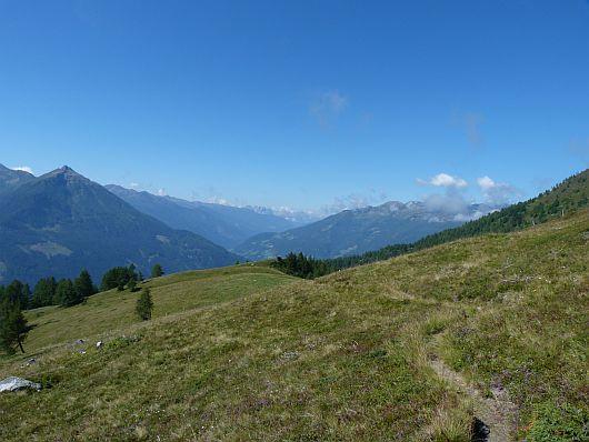 Eine Almfläche wurde hier durchlaufen. Links die Berge der Kreuzeckgruppe, rechts die Goldberggruppe und am Horizont die Lienzer Dolomiten.